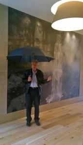 El alemán Stephan Riedel posa frente a la ampliación de una foto que tomó en el Salto del Tequendama y que adorna el tercer piso del EK Hotel, en Bogotá. Foto: Cortesía de Stephan Riedel.