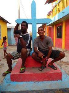 Dionis Cordales (izquierda) y su hermano Guillermo conversan bajo la cruz pintada de azul, el monumento más importante de Santa Cruz del Islote. Foto: Juan Uribe